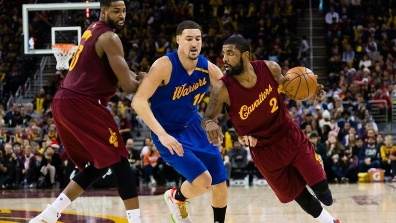 Kyrie Irving (R) of the Cleveland Cavaliers drives around Klay Thompson of the Golden State Warriors during the second half, at Quicken Loans Arena in Cleveland, Ohio, on December 25, 2016