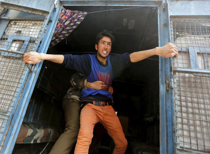 A supporter of Kashmiri lawmaker Rashid attempts to jump from a police vehicle after he was detained
