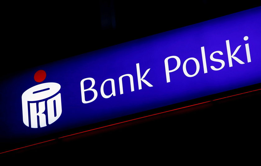 A woman walks outside an entrance to the PKO BP bank headquarters, Poland's largest lender, in Warsa