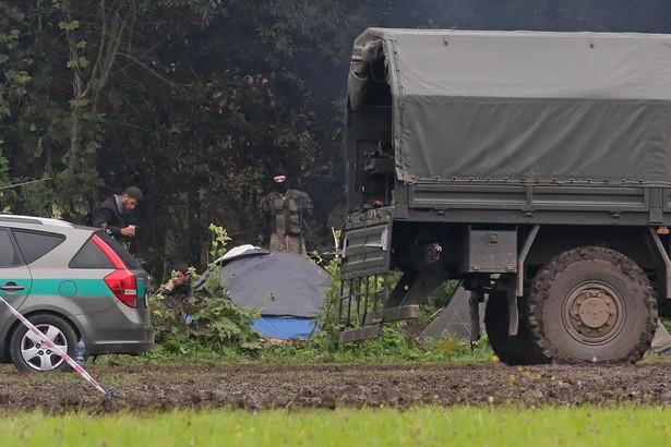 Uchodźcy i funkcjonariusz białoruski na polsko-białoruskiej granicy w pobliżu miejscowości Usnarz Górny