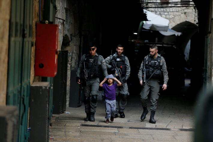Israeli border policemen escort a boy away from a blocked alley after a stabbing attack inside the o