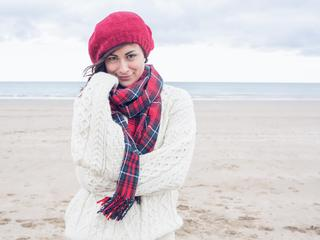 Cute smiling young woman in stylish warm clothing