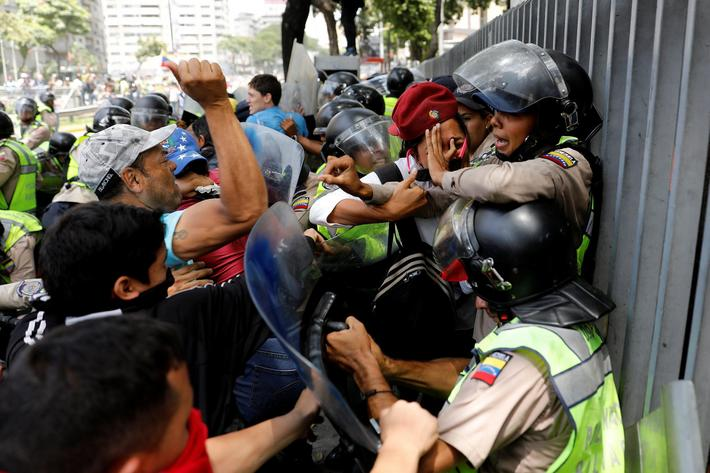 Demonstrators scuffle with security forces during an opposition rally in Caracas