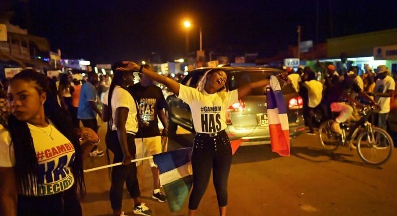 People celebrate in the streets of Banjul on January 21, 2017 after hearing of the confirmed departure of former Gambian leader Yahya Jammeh from the country