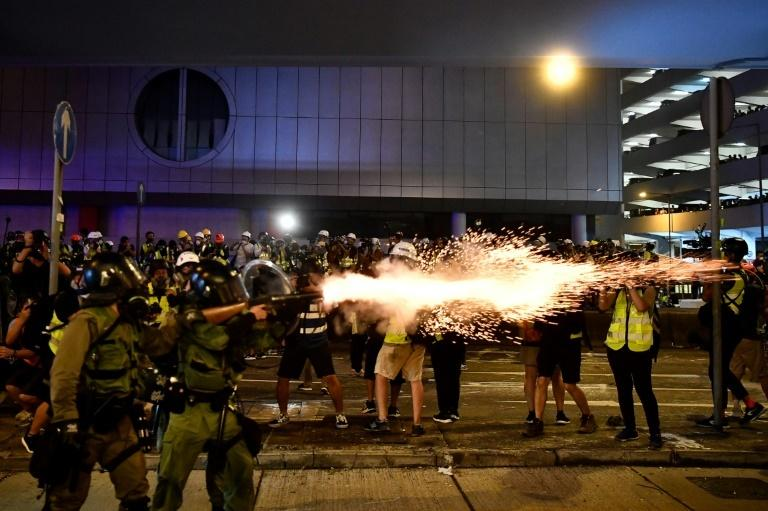 A policeman fires tear gas at protesters