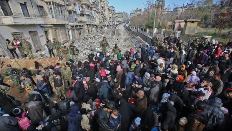 Syrian residents fleeing the violence gather at a checkpoint, manned by pro-government forces, in the Maysaloun neighbourhood of the northern embattled Syrian city of Aleppo on December 8, 2016