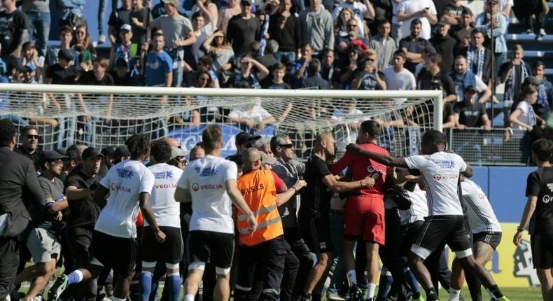 Bastia supporters invade the pitch to try to attack Lyon's Portuguese goalkeeper Anthony Lopes (in red) and others players during their warm-up prior to the French Ligue 1 match at the Armand Cesari stadium in Bastia, Corsica on April 16, 2017