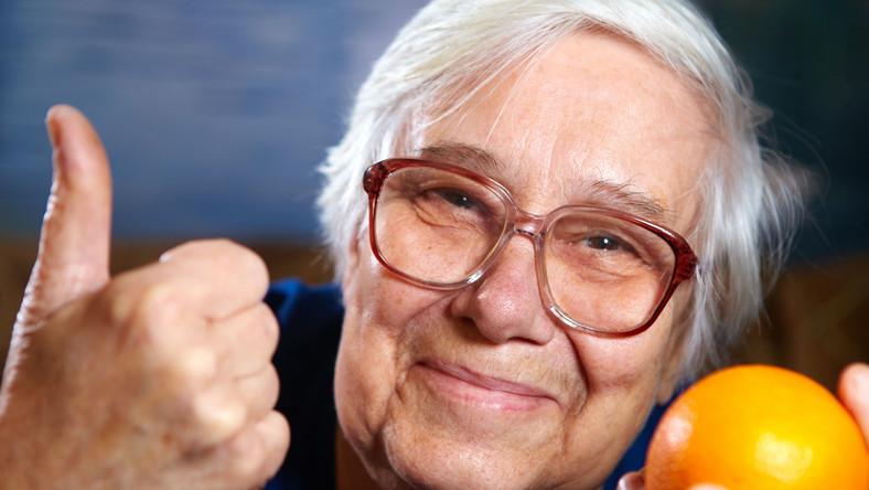 Starsza kobieta trzyma pomarańczę