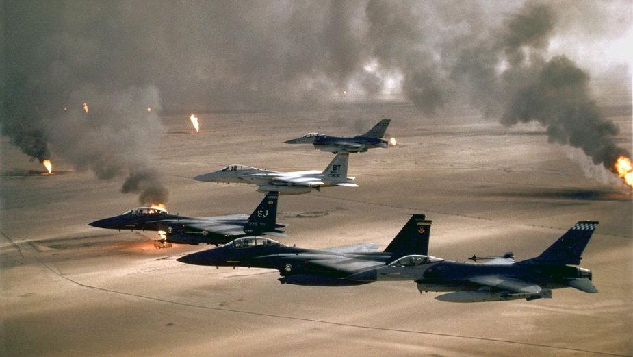 Samoloty F-16A, F-15C i F-15E przelatują nad płonącymi polami naftowymi, operacja Pustynna Burza (domena publiczna).