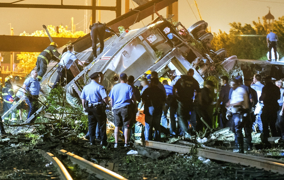 Rescue workers climb into the wreckage of a crashed Amtrak train in Philadelphia