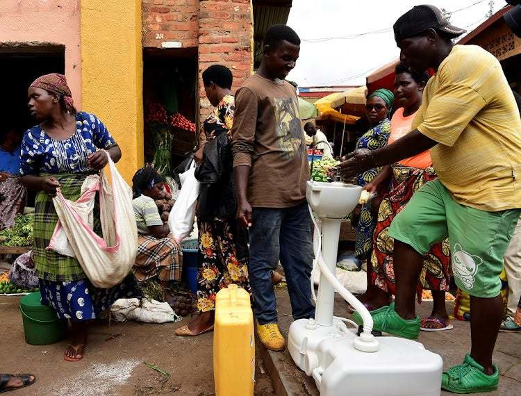 Rwandans wash their hands in public taps provided by governement to halt spread of coronavirus. (TimesLIVE)
