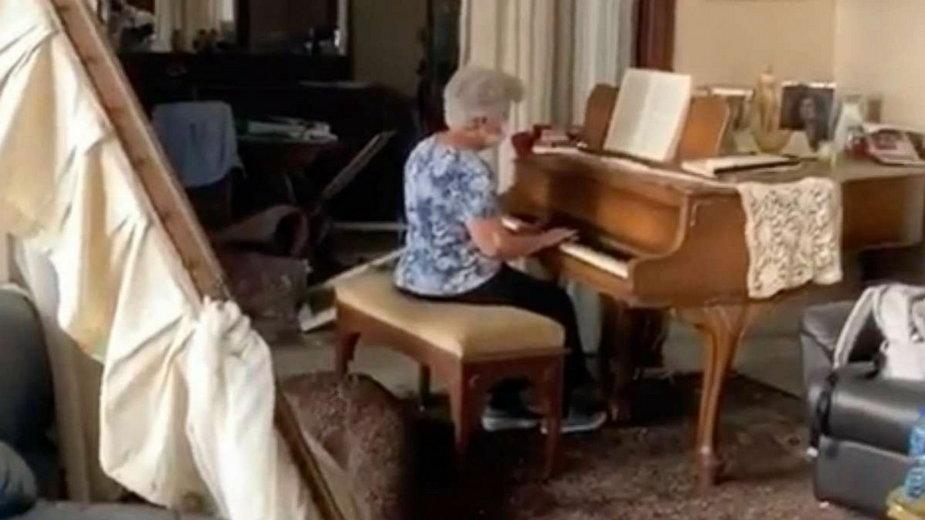 Starsza kobieta gra na fortepianie w zniszczonym mieszkaniu