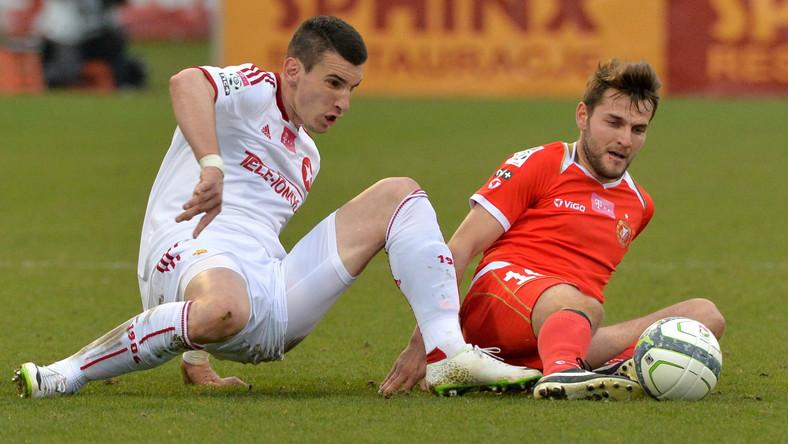 Zawodnik Widzewa Łódź Mateusz Cetnarski (P) walczy o piłkę z Gordanem Bunozą (L) z Wisły Kraków