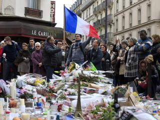 People pay tribute to victims outside Le Carillon restaurant, one of the attack sites in Paris