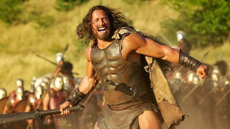 """– Od bardzo, bardzo dawna marzyłem o filmie o Herkulesie. To postać silnie zakorzeniona w naszej kulturze i ważna dla mnie osobiście. Chcieliśmy jednak pokazać publiczności Herkulesa, jakiego jeszcze nie widziała –mówi Dwayne Johnson. –Gdy go poznajemy, jest wygnańcem, walczy tylko dla złota. Musi zmagać się ze swoimi demonami i stać się takim, jakim ludzie oczekują, że powinien być. """"The Rock"""" na potrzeby roli, musiał nie tylko ostro trenować (co w końcu nie jest dla niego pierwszyzną), ale także poddawać się na planie długotrwałym zabiegom charakteryzatorskim: – Szło o całkowitą transformację: postarzono mnie, wydłużono włosy, zmatowiono skórę, zakryto tatuaże, a dodano blizny, wiele blizn – opowiada. – Było wspaniale, chociaż siedzenie bez ruchu przez cztery godziny dziennie, przez 95 dni, by się ucharakteryzować, to był naprawdę ból!"""