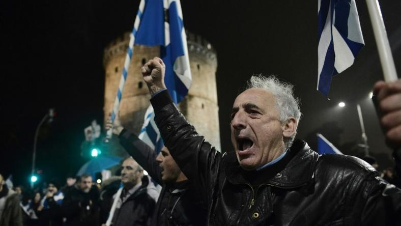 People hold Greek flags and shout slogans in Thessaloniki on December 14, 2018, as they protest Macedonia's name change, which they object to because of the northern Greek province of the same name