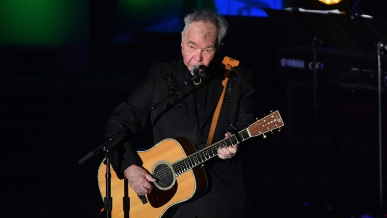 """US singer-songwriter John Prine, pictured June 2019, has been hospitalized and intubated due to a """"sudden onset of Covid-19 symptoms,"""" according to his family"""