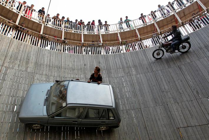 "Stunt performers ride a motorcycle and a car on the walls of the ""Well of Death"" at the Magh Mela fa"