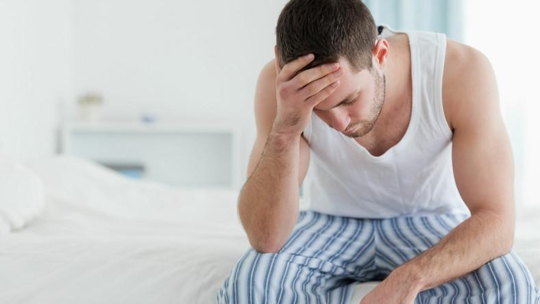 Mężczyzna siedzi na łóżku, ma problem