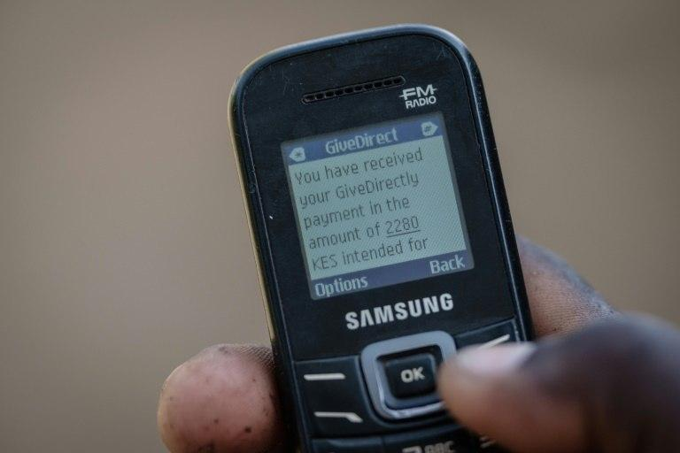 A villager shows his mobile phone's monitor displaying a message confirming the universal basic income transaction, 2,250 shillings per month ($22,19 euros)