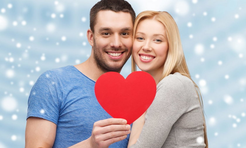 happy couple with red heart shape hugging outdoors