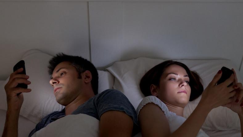 Kobieta i mężczyzna w łóżku trzymają smartfony