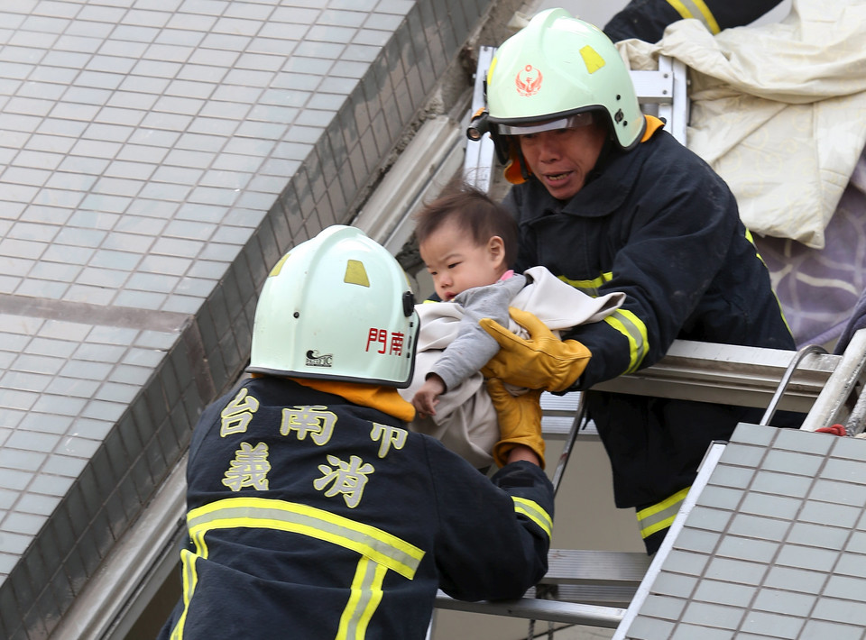 Rescue workers remove a baby from the site where a 17-storey apartment building collapsed after an earthquake hit Tainan