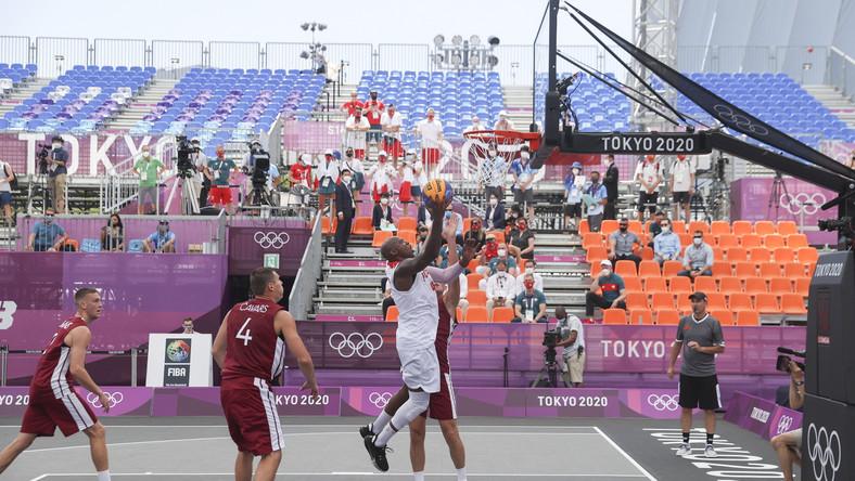 Michael Hicks (C, biały strój) podczas meczu z Łotwą na igrzyskach olimpijskich