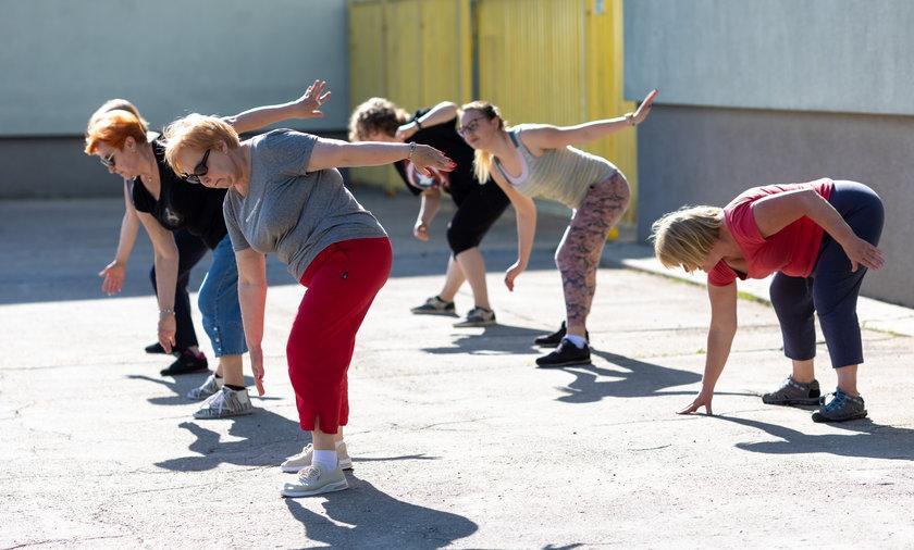Seniorzy ćwiczą na świeżym powietrzu.