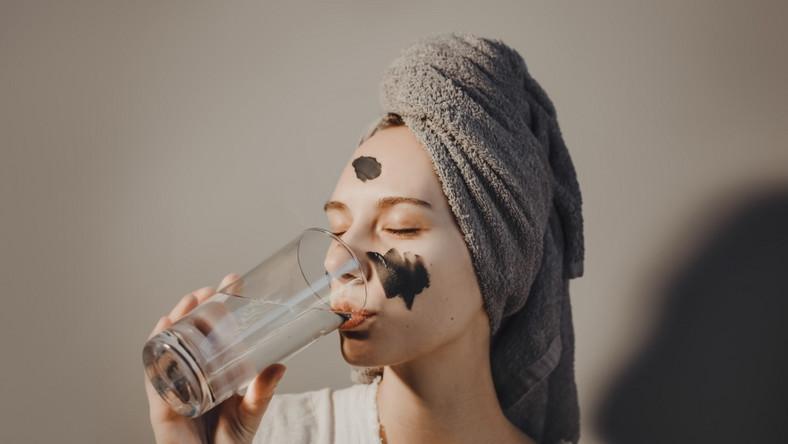 Kobieta z maseczką na twarzy pije napój kolagenowy