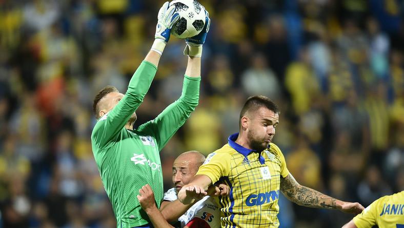 Zawodnicy Arki Gdynia Aleksandar Kolev (P) i bramkarz Matus Putnoscky (L) oraz Łukasz Trałka (2-L) z Lecha Poznań