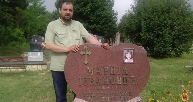 Otac pored nadgrobnog spomenika ćerki