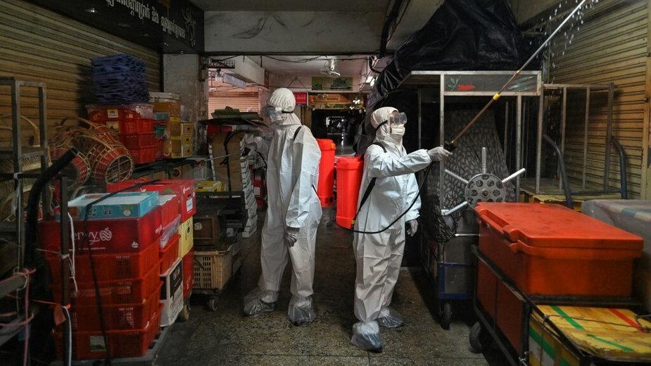 Pracownicy rozpylają środki dezynfekujące na targu Orussey, Phnom Penh, 4 kwietnia 2021 r