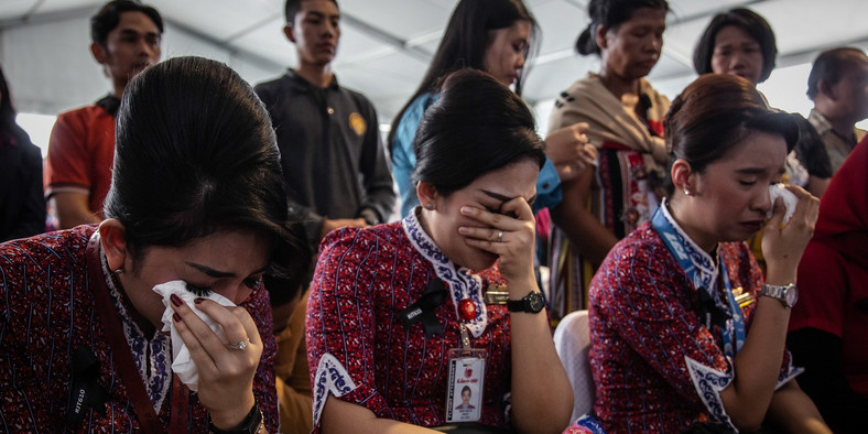 Families and colleagues of victims of Lion Air flight JT 610 cry on deck of Indonesian Navy ship KRI Banjarmasin during visit and pray at the site of the crash on November 6, 2018 in Karawang, Indonesia.