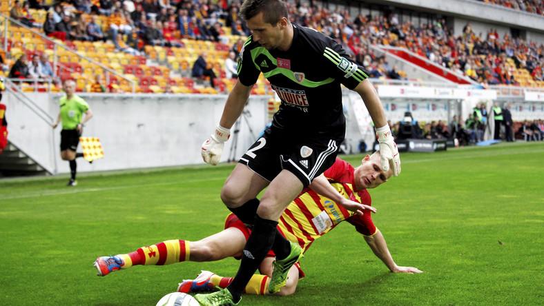Piłkarz Jagiellonii Białystok Mateusz Piątkowski (z tyłu) w ataku na bramkę Dariusza Treli z Piasta Gliwice podczas meczu grupy B polskiej Ekstraklasy