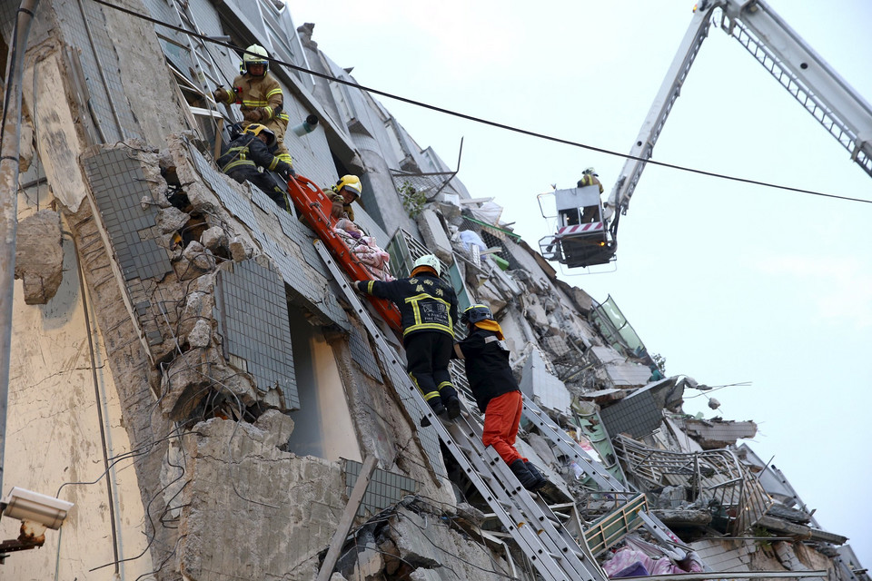 Rescue personnel work at a damaged building after an earthquake in Tainan