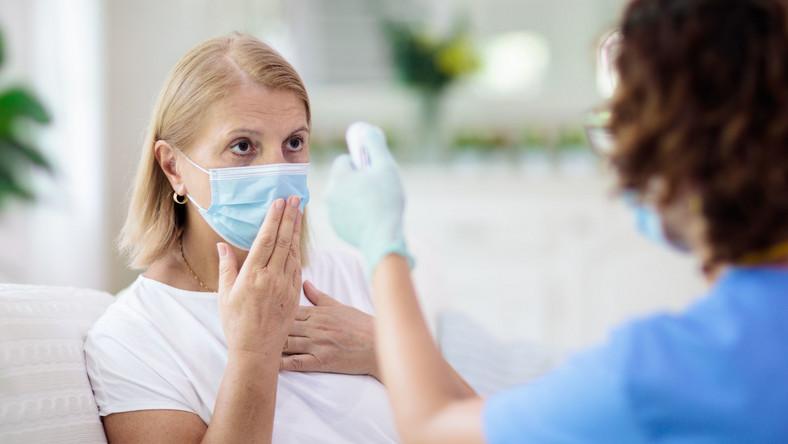 Badanie temperatury, pacjent w maseczce