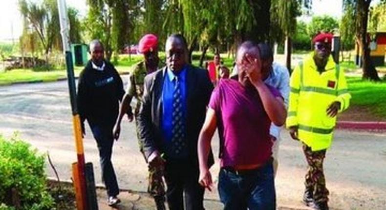 Major Peter Mugure being arrested by military police officers