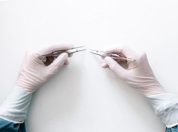 stock-photo-microsurgery-surgeon-using-microscopic-tweezers-against-white-background-1035429499