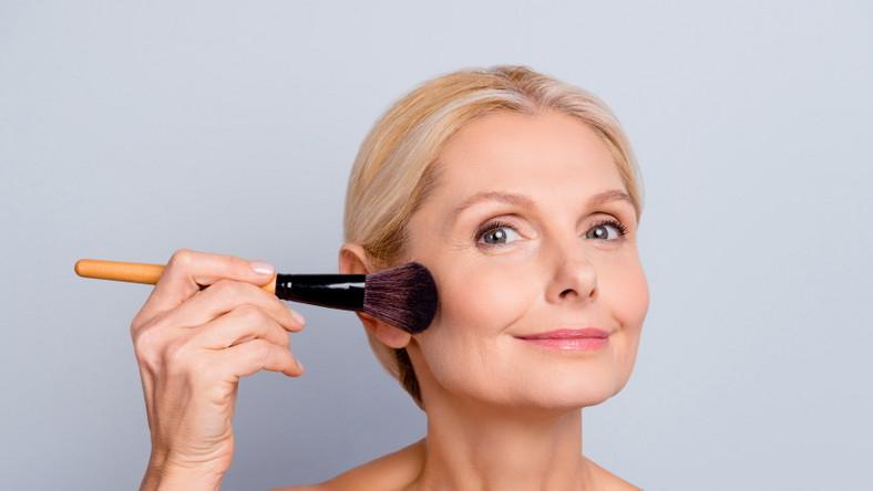 Dojrzała kobieta robi makijaż