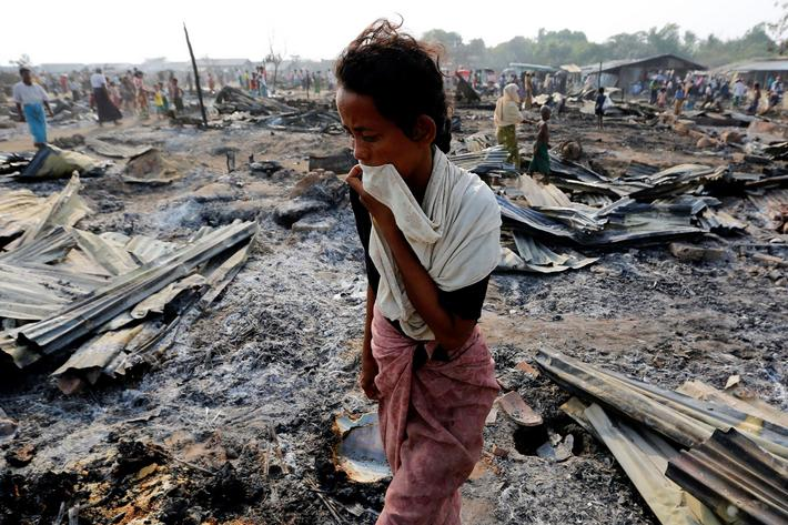 A woman walks among debris after fire destroyed shelters at a camp for internally displaced Rohingya