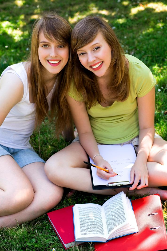 Two young women studying outdoors