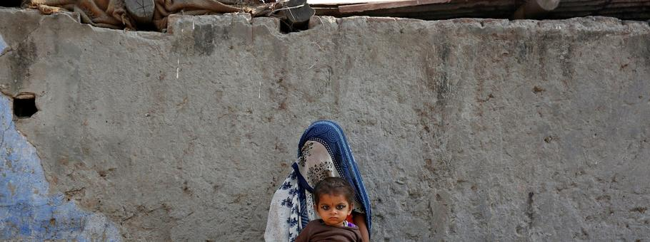 A woman rests with her child while working as a day labourer in Delhi