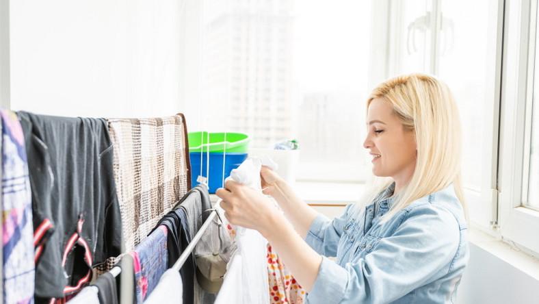 Kobieta rozwiesza pranie na balkonie