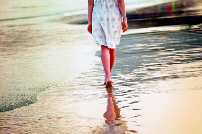 stock-photo-a-lonely-girl-is-walking-along-island-coastline-and-has-reflection-on-wet-sand-267916559