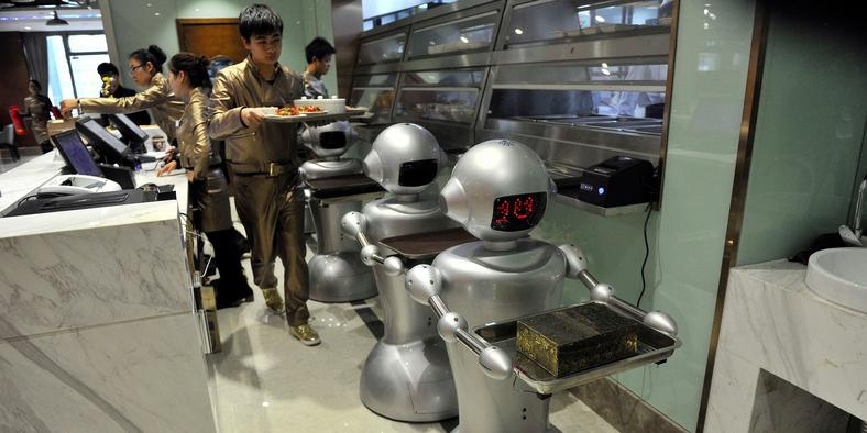 A man puts dishes on robots for delivery at a restaurant in Hefei, Anhui province, December 26, 2014.