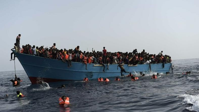 Migrants wait to be rescued in the Mediterranean Sea about 12 nautical miles north of Libya on October 4, 2016