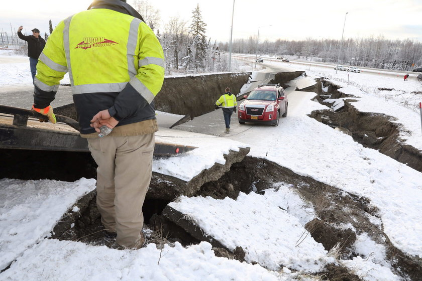 A vehicle lies stranded on a collapsed roadway near the airport after an earthquake in Anchorage