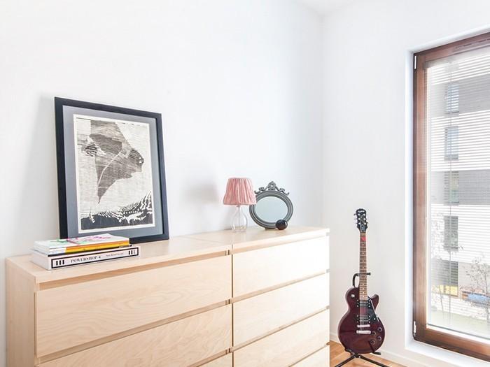 W pomieszczeniu znalazła się narożna szafa garderobiana, która wtapia się w białe ściany oraz obija światło w połyskliwych frontach.