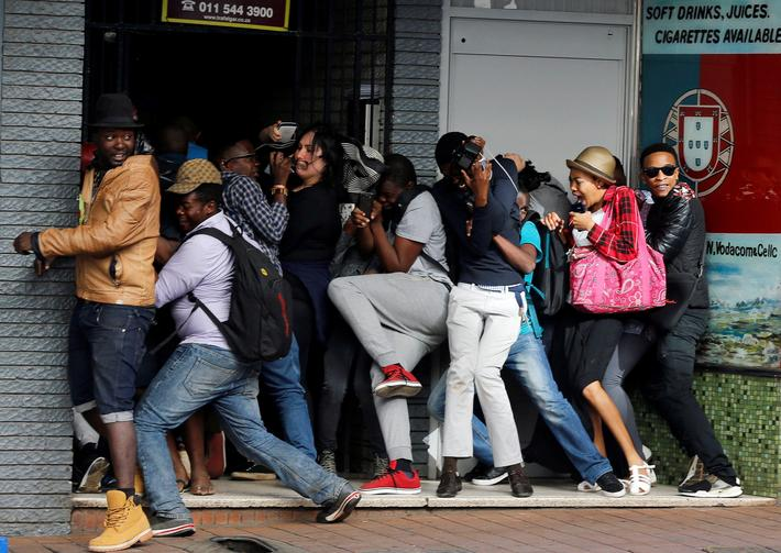 Students demanding free education react as they are fired at by riot police officers during a protes